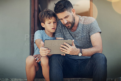 Buy stock photo Shot of a father and son spending the day together at home
