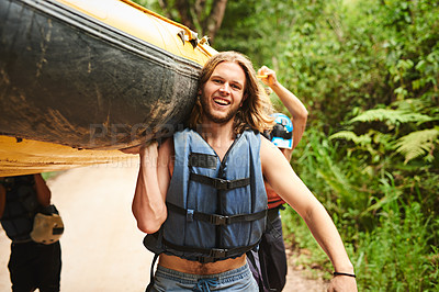 Buy stock photo Cropped portrait of a handsome young man and his friends carrying their raft towards the water