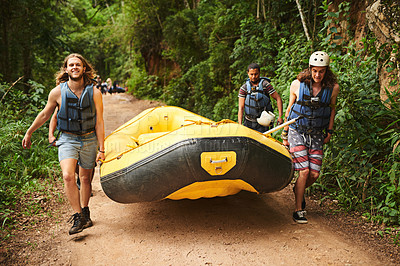 Buy stock photo Full length portrait of a handsome young man and his friends carrying their raft towards the water