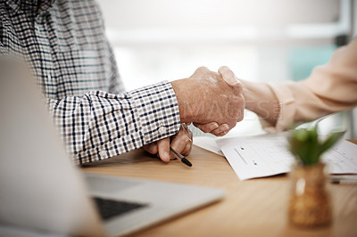 Buy stock photo Cropped shot of an unrecognizable senior couple shaking hands while working on their finances at home