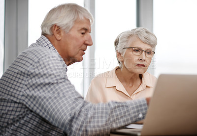 Buy stock photo Shot of a senior couple working on their finances using a laptop