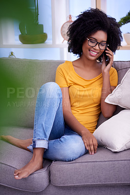 Buy stock photo Shot of an attractive young woman using a mobile phone while relaxing on the sofa at home