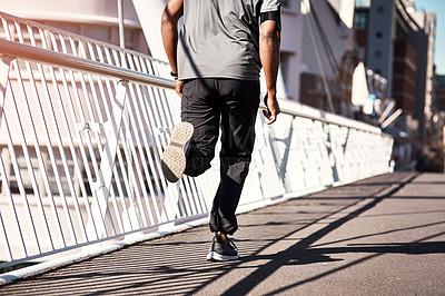 Buy stock photo Rearview shot of an unrecognizable young man exercising outdoors in the city