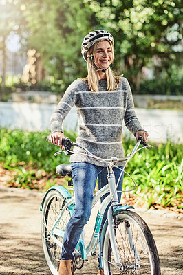 Buy stock photo Shot of a woman out cycling at the park on a sunny day