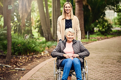 Buy stock photo Shot of a woman pushing her mother around in her wheelchair