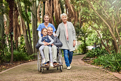 Buy stock photo Shot of a female nurse spending the day outdoors with her patient and his family