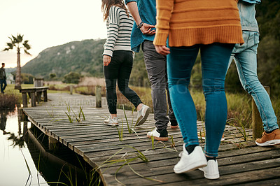 Buy stock photo Cropped shot of unrecognizable friends walking on a pier outside