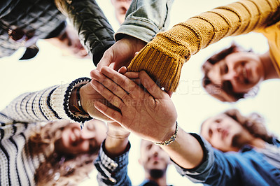 Buy stock photo Low angle shot of a group of friends hands stacked together outside