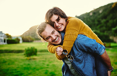 Buy stock photo Cropped shot of a young man giving his girlfriend a piggyback ride outdoors