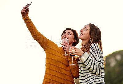 Buy stock photo Cropped shot of female best friends taking a selfie together outdoors