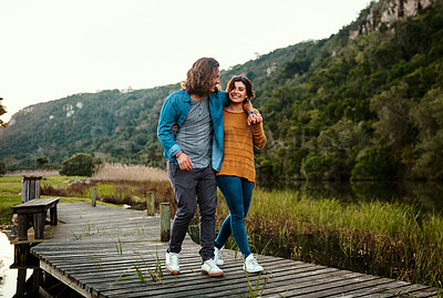 Buy stock photo Shot of a young couple walking on a pier outdoors