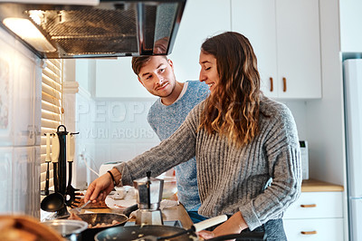 Buy stock photo Cropped shot of a young attractive couple making food together in the kitchen at home