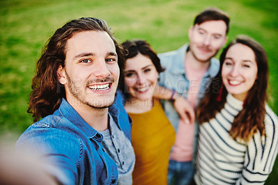 Buy stock photo Cropped shot of a group of friends taking a selfie outdoors