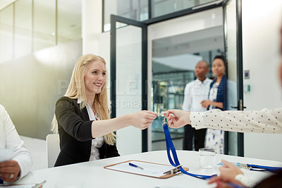 Buy stock photo Shot of a cheerful businesswoman handing over a access card to a client to attend a seminar during the day