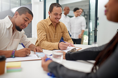 Buy stock photo Shot of a group of cheerful young businessmen signing forms to attend a seminar inside of a building during the day