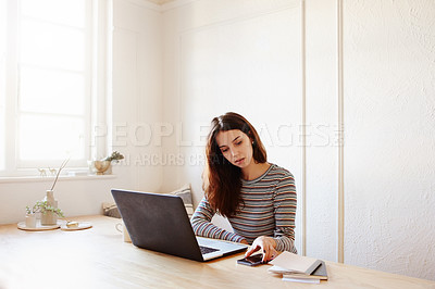 Buy stock photo Shot of an attractive young woman using a mobile phone and laptop while working at home