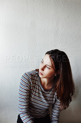 Buy stock photo Shot of an attractive young woman looking thoughtful at home