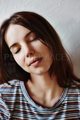 Buy stock photo Shot of an attractive young woman posing against a wall at home