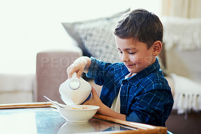 Buy stock photo Shot of an adorable little boy pouring milk into his cereal at home