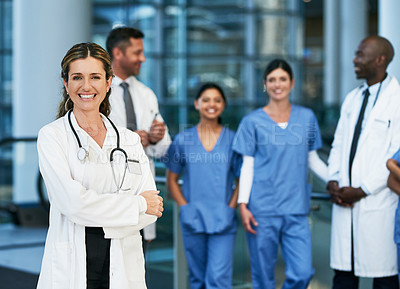 Buy stock photo Portrait of a mature doctor standing in a hospital with her colleagues in the background