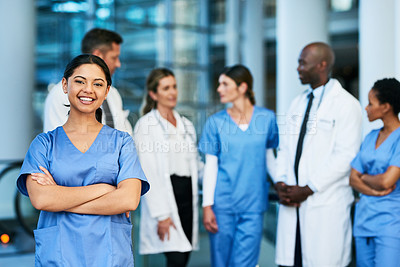 Buy stock photo Portrait of a young medical practitioner standing in a hospital with her colleagues in the background