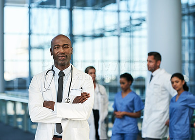 Buy stock photo Portrait of a mature doctor standing in a hospital with his colleagues in the background