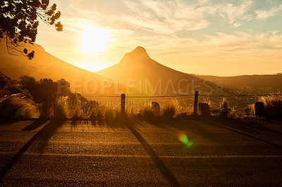 Buy stock photo Shot of the sun setting over the mountains