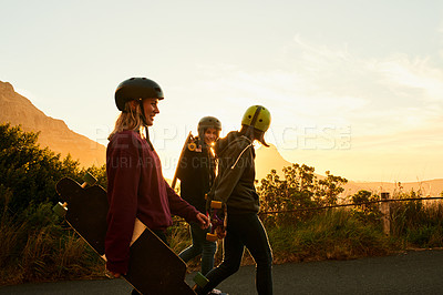 Buy stock photo Shot of three female friends out with their skateboards at sunset