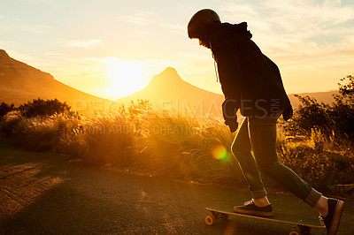 Buy stock photo Shot of a young woman out skating at sunset