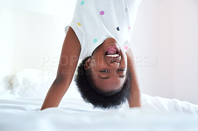 Buy stock photo Cropped portrait of an adorable little girl doing a handstand on her bed at home