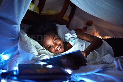 Buy stock photo Cropped portrait of an adorable little girl using a digital tablet while lying in bed