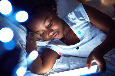 Buy stock photo Cropped shot of an adorable little girl using a digital tablet while lying in bed