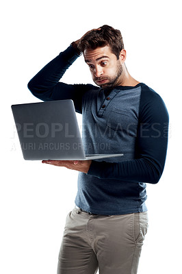 Buy stock photo Studio shot of a handsome young man using a laptop and looking anxious against a white background