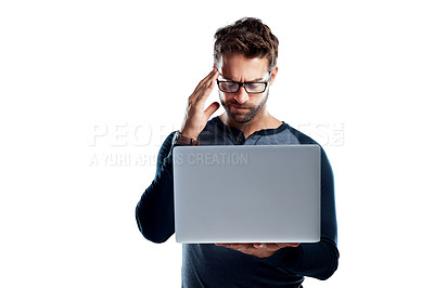 Buy stock photo Studio shot of a handsome young man using a laptop and looking stressed against a white background