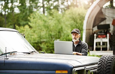 Buy stock photo Shot of a mature man using a laptop while working on a farm