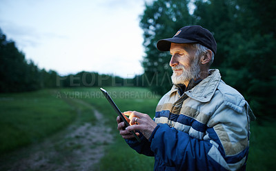 Buy stock photo Shot of a mature man using a digital tablet while working on a farm