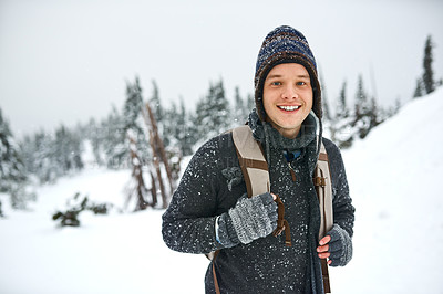 Buy stock photo Shot of a handsome young man spending the day out in the snow