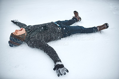 Buy stock photo Shot of a young man lying in the snow making a snow angel