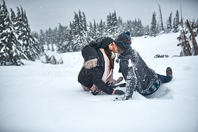 Buy stock photo Shot of a couple kissing while spending the day in the snow