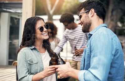 Buy stock photo Shot of a young couple having beers at a barbecue with their friends
