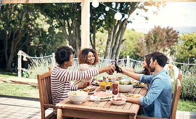 Buy stock photo Shot of a group of friends toasting with beers while having a meal together outdoors