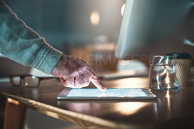 Buy stock photo Closeup shot of a businessman using a digital tablet in an office at night