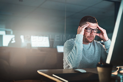 Buy stock photo Shot of a mature businessman looking stressed out while working late on a computer in an office