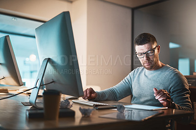 Buy stock photo Shot of a mature businessman working late on a digital tablet and computer in an office