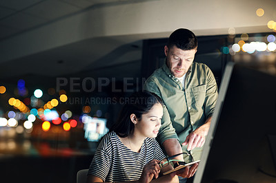 Buy stock photo Shot of two designers working late on a digital tablet in an office