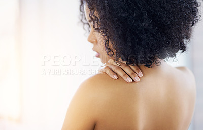 Buy stock photo Rearview shot a young woman touching her bare shoulder