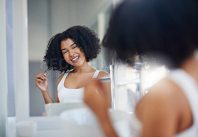 Buy stock photo Cropped shot of a beautiful young woman styling her hair in her bathroom