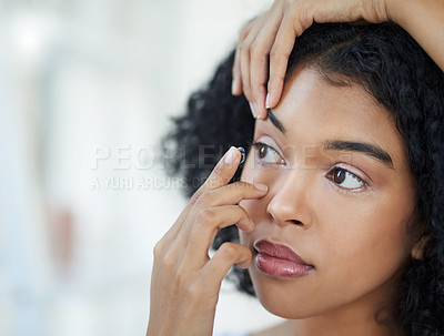 Buy stock photo Cropped shot of a beautiful young woman putting in her contact lenses at home