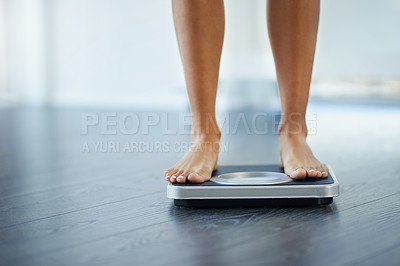 Buy stock photo Shot of an unrecognizable woman weighing herself at home
