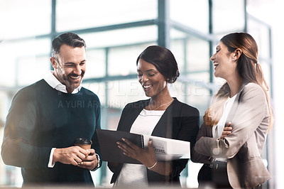 Buy stock photo Shot of a group of businesspeople discussing paperwork in a modern office